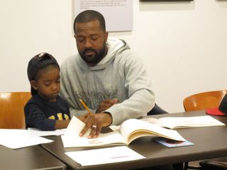 Brian Carson and son Khaliq learn about family history at the Anacostia Community Museum.