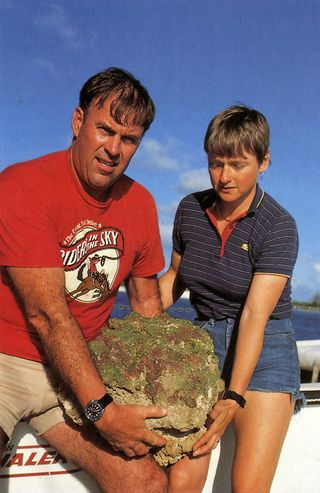 On the deck of the submersibles mother ship the R/V Johnson, Mark and Diane Littler hold a crustose coralline growing attached a rock substrate collected from a depth of 268 meters off the northern border of San Salvadore Island, Bahamas, in October 1983.