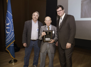 Botany Chair Warren Wagner and Kirk Johnson, Sant Director of the National Museum of Natural History, present Aaron Goldberg with the Career Contributions to Science Award. The plaque contains a piece of stone from the building of Natural History. (photo by Brittany M. Hance, Smithsonian)