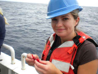 Jamie on-deck inspecting a small crustacean