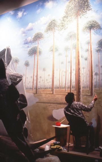 Robert Hynes painting a mural behind the models of Stegosaurus, which is draped in plastic.