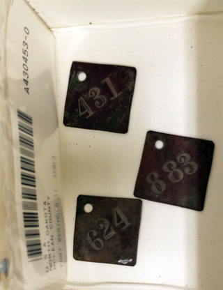 Photo of brass number tags in artifact storage box