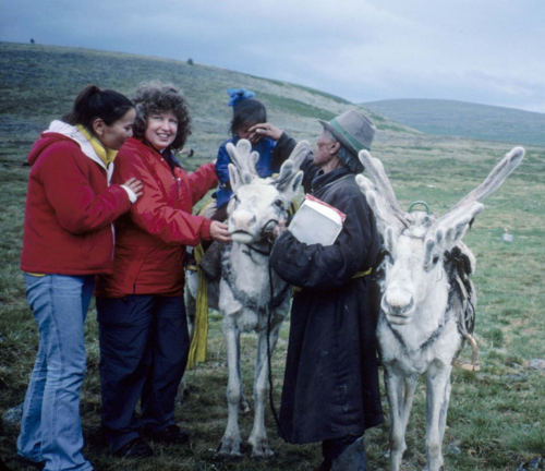 Paula DePriest (second from left) examines the reindeer mount of a young Tsaatan girl with her grandfather, Tsaatan Herder Sanjin, and an interpreter (Photo by Sue Lutz)