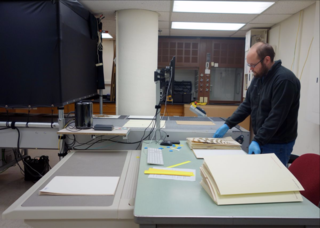 Specimens from the United States National Herbarium are placed on a conveyer belt for rapid digitization. (photo by Ingrid Lin)
