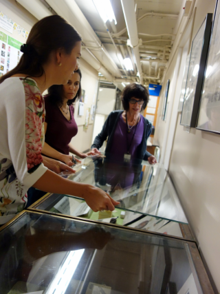 Melinda Peters, Rose Gulledge, and Alice Tangerini disassemble a display case to prepare it for new material. (photo by Ingrid Lin)