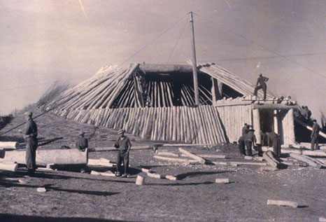 1930s photo of Civilian Conservation Corps crew working on the construction of an earth lodge at On-a-Slant Village
