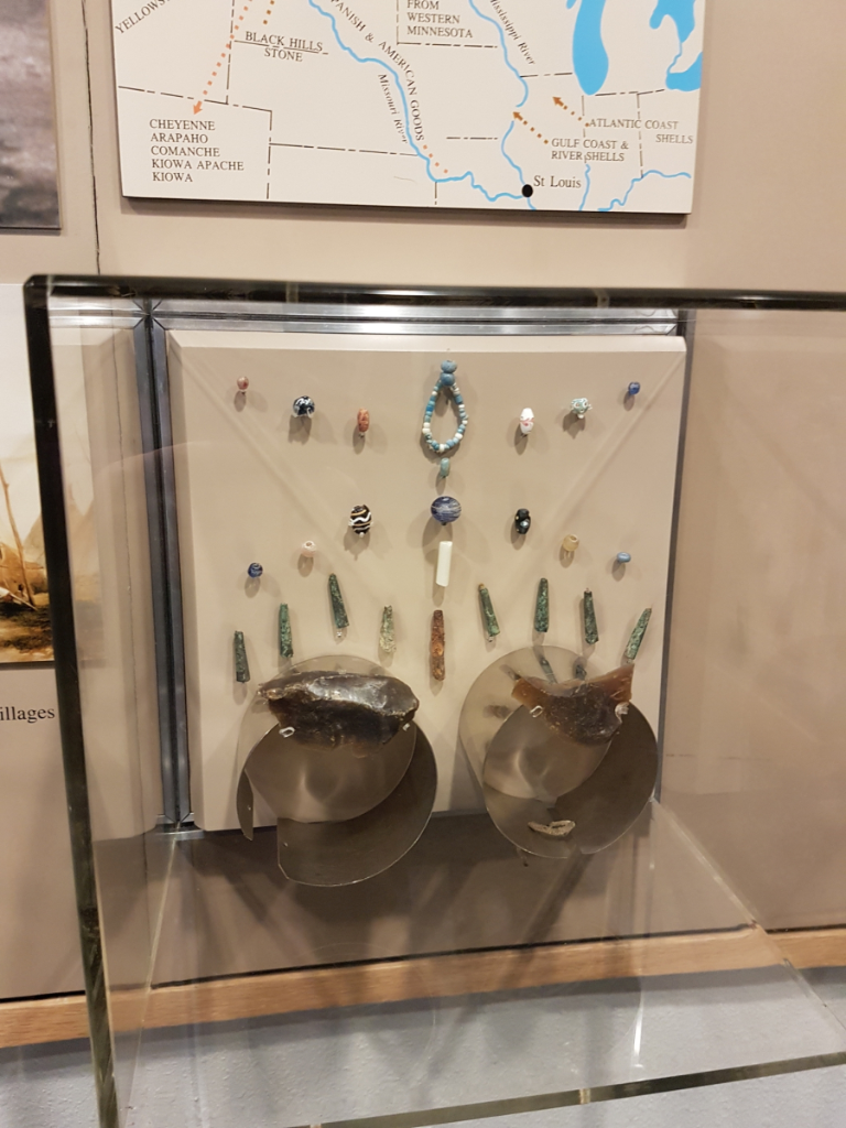 An exhibit case showing some local artifacts, including Knife River flint, glass beads, and metal tinklers.