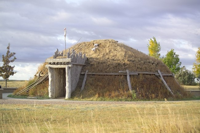 A photo of the outside of the earth lodge at Knife River Indian Villages, during nicer weather. Photo: National Park Service.