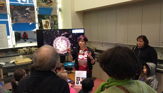 Cheryl Lewis Ames talking to some curious visitors, with an upside-down jellyfish on the monitor in the background.