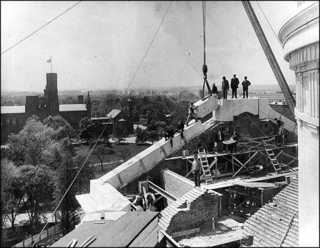 """On May 11, 1909, workers set the final stone on the National Museum of Natural History building.  Construction of the museum began in 1904, and the granite structure was completed in 1911.  The background of this photo shows the first Smithsonian Institution building, known as """"the Castle."""""""