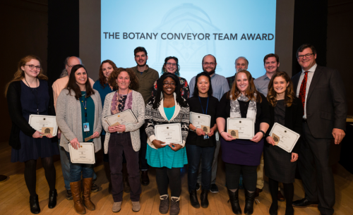 "Recipients of the ""Botany Conveyor Team Award"" (left to right): Haley Wallace, Chris Tuccinardi, Laura Tancredi, Rebecca Snyder, Sylvia Orli, Nick Silverson, Rochelle Safo, Amanda Robinson, Ingrid Lin, Peter Olson, Tom Hollowell, Mindy Shull, Justin Donaldson, and Katie Altizer, with NMNH Sant Director Kirk Johnson. (photo by the Smithsonian Institution)"