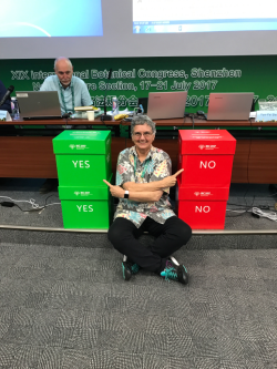 "Vicki Funk at the Nomenclature Section of the XIX IBC in Shenzhen, China, with the ""yes"" and ""no"" voting boxes. (photo by Sandra Knapp)"
