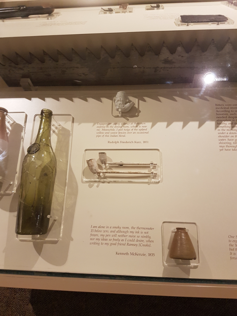 Photo of a display case showing clay pipes, a glass bottle, and an inkwell, alongside passages from Rudolph Friederich Kurz's journal, and a letter from Kenneth McKenzie to Ramsay Crooks