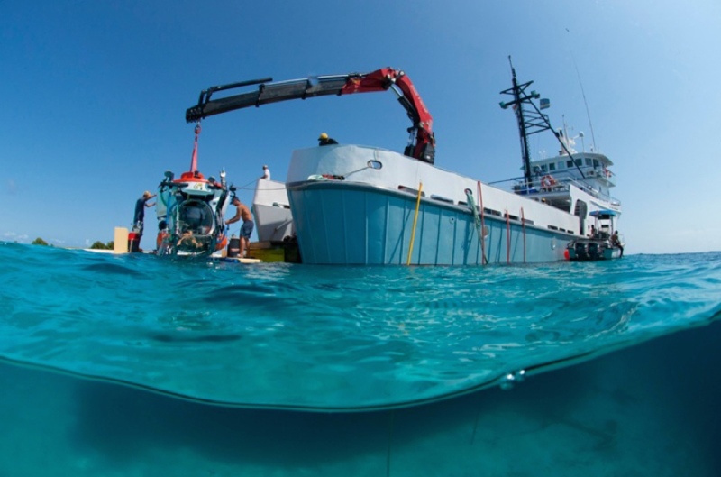 Deployment of the Curasub submersible from its shipboard platform, the R/V Chapman at Klein Curacao, February 2013. The availability of the R/V Chapman now provides scientists the ability to explore deep reefs beyond the reef slope off the Curacao Sea Aquarium. Photo by Barry Brown.