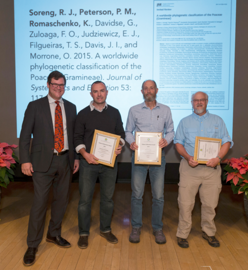 NMNH Sant Director Kirk Johnson presents a 2016 Science Achievement Award to Konstantin Romaschenko, Paul Peterson, and Robert Soreng. (photo by the Smithsonian Institution)