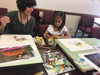 Alice Tangerini gives painting tips to youth art winner, Sanah Hutchins. (photo by Nabeeha Kazi)