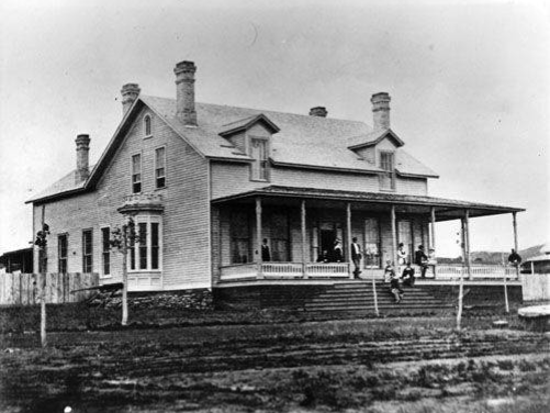Figure 13: Several people on the porch and steps of the Custer house, sometime between 1873 and 1876.