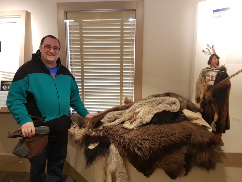 A man standing inside an exhibit space smiles at the camera, his left hand touching a pile of furs/hides from various animals, including bison and bear.