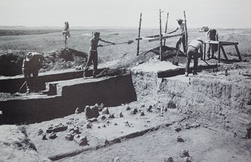 A black and white photo of a partially excavated site, with five men shoveling and screening soil.