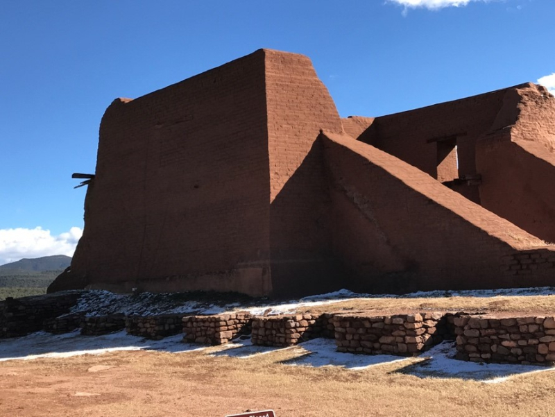 Side view of architectural remains against a blue sky. Some snow on the ground.