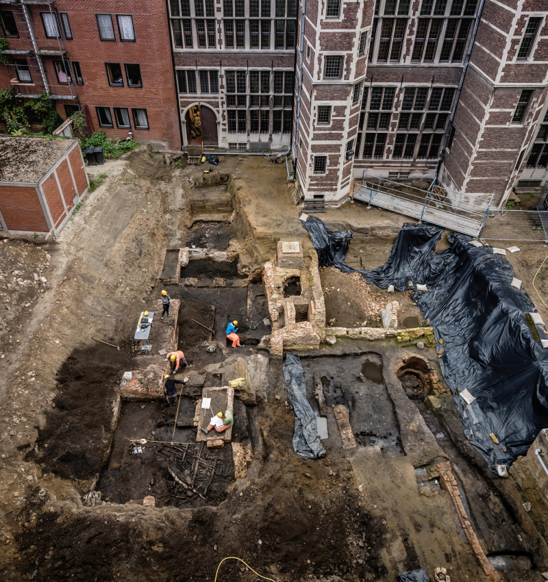 Aerial view of the site, showing remains of brick walls and some wooden construction, including archaeologists in hard hats