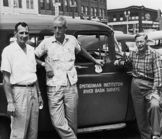 "Black and white photo of three men posing in front of a vehicle with ""Smithsonian Institution River Basin Surveys"" written on the passenger side door"
